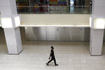 A lone man wearing a protective face mask walks in a mall along the Orchard Road shopping belt in Singapore, Friday, April 10, 2020. The Singapore government put in place