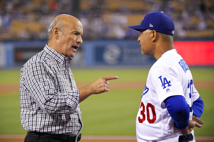 Los Angeles Dodgers co-owner Stan Kasten, left, talks with manager Dave Roberts prior to the team's baseball game against the Colorado Rockies on Friday, Sept. 20, 2019, in Los Angeles. (AP Photo/Mark J. Terrill)