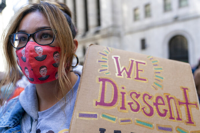 A demonstrator wears a Ruth Bader Ginsberg face mask during a Women's March rally outside the New York Stock Exchange, Saturday, Oct. 17, 2020, in New York.  Dozens of Women's March rallies were planned from New York to San Francisco to signal opposition to President Donald Trump and his policies, including the push to fill the seat of late Supreme Court Justice Ruth Bader Ginsburg before Election Day. (AP Photo/Mary Altaffer)