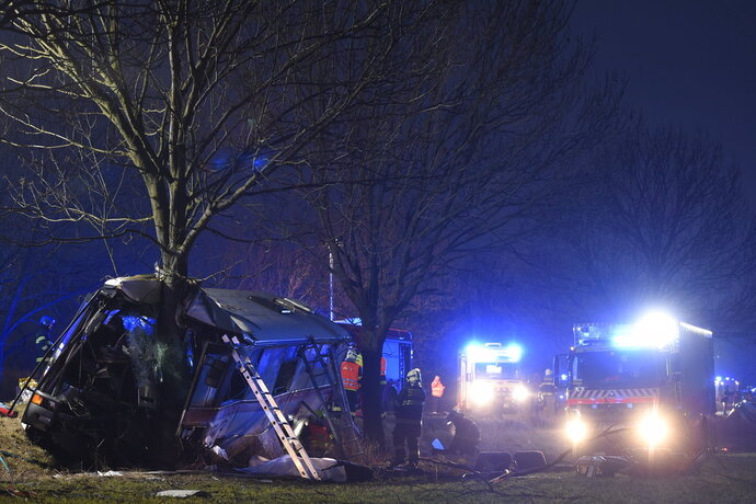 Rescue workers and firemen work at a bus after its collision with a car at Horomerice near Prague, Czech Republic, Friday 12, 2018. The accident claimed three lives and 30 injuries. At least ten people have serious injuries. (Ondrej Deml/CTK via AP)