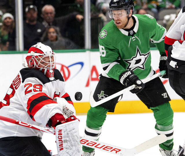 New Jersey Devils goaltender Mackenzie Blackwood (29) deflects the puck as Dallas Stars center Joe Pavelski (16) applies pressure in the first period of an NHL hockey game, Tuesday, Dec. 10, 2019, in Dallas. Pavelski scored Dallas' second goal of the game on the deflection. (AP Photo/Jeffrey McWhorter)