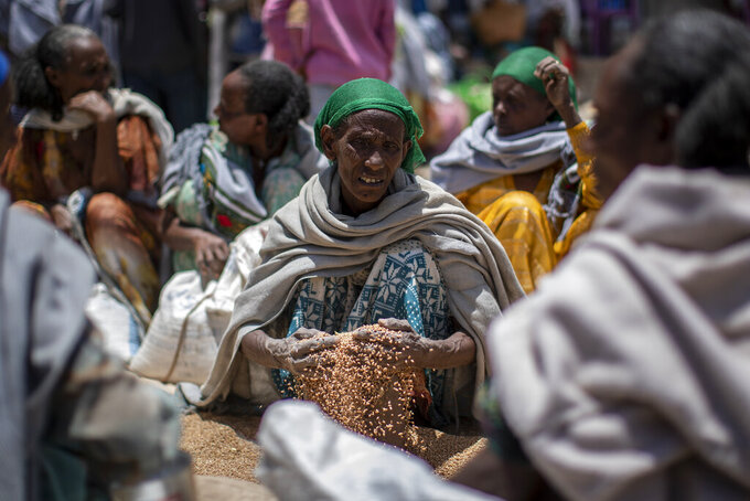 In this Saturday, May 8, 2021, photo, an Ethiopian woman scoops up grains of wheat after it was distributed by the Relief Society of Tigray in the town of Agula, in the Tigray region of northern Ethiopia. As the United States warns that up to 900,000 people in Tigray face famine conditions in the world's worst hunger crisis in a decade, little is known about vast areas of Tigray that have been under the control of combatants from all sides since November 2020. With blocked roads and ongoing fighting, humanitarian groups have been left without access. (AP Photo/Ben Curtis)