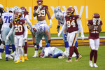 Players reacting to seeing Dallas Cowboys quarterback Andy Dalton (14) lying on the ground after getting hit by Washington Football Team inside linebacker Jon Bostic (53) in the second half of an NFL football game, Sunday, Oct. 25, 2020, in Landover, Md. (AP Photo/Susan Walsh)