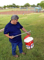 In this May 8, 2019, photo, Hector Aguilar uses a claw grabber extension to remove a hypodermic needle from one of the baseball fields at Atrisco Park, home of the Atrisco Valley Little League, in Albuquerque, N.M. The little league park is fighting a battle against discarded syringes with attached hypodermic needles amid the region's outgoing opioid epidemic. (Jim Thompson/The Albuquerque Journal via AP)