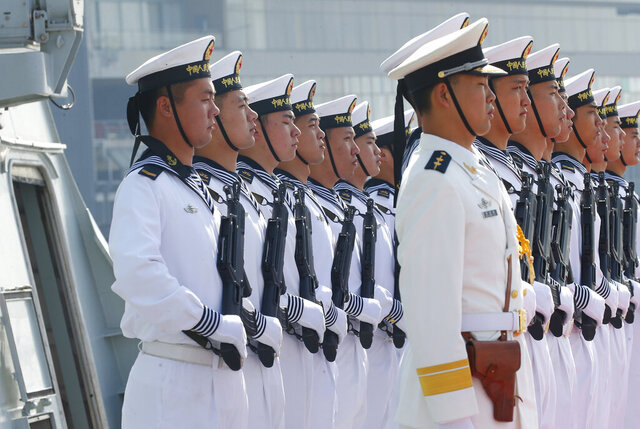 FILE - In this Jan. 17, 2019, file photo, Chinese People's Liberation Navy sailors stand in formation on the deck of a type 054A guided missile frigate
