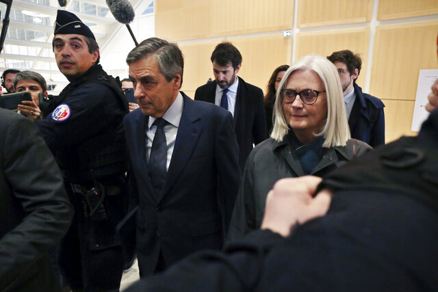 France's former Prime Minister Francois Fillon, left, and his wife Penelope, arrive at the Paris courthouse, in Paris, Wednesday, Feb. 26, 2020. He could have been president of France. Instead, former Prime Minister Francois Fillon is going on trial to face fraud charges after he used public funds to richly pay his wife and children for work they allegedly never performed. (AP Photo/Thibault Camus)