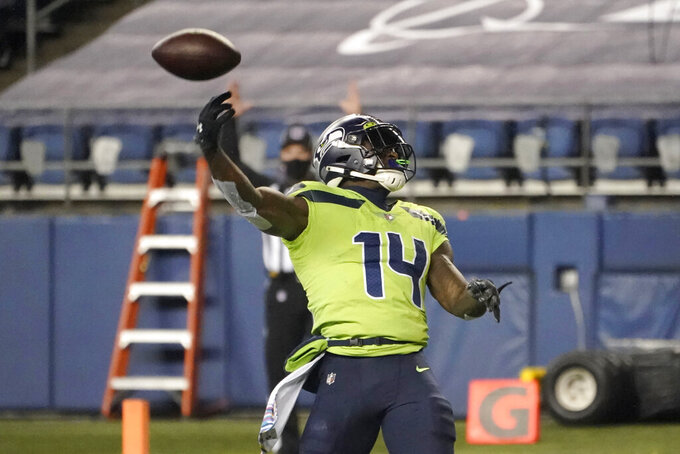 Seattle Seahawks' DK Metcalf tosses away the ball after his 13-yard touchdown pass reception against the Minnesota Vikings during the second half of an NFL football game, Sunday, Oct. 11, 2020, in Seattle. (AP Photo/Ted S. Warren)