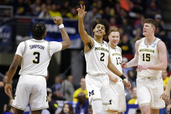 Michigan's Jordan Poole (2) celebrates with teammates including Zavier Simpson (3) after scoring a basket against Florida and drawing a foul, during the second half of a second round men's college basketball game in the NCAA Tournament, in Des Moines, Iowa, Saturday, March 23, 2019. (AP Photo/Nati Harnik)