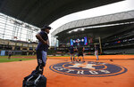 Tampa Bay Rays bullpen catcher Mayo Acosta, left, watches as grounds crew members cover the field at Minute Maid Park with a tarp after the roof failed to close and rain moved into the area, Thursday, Oct. 3, 2019, in Houston. The Rays are scheduled to play the Houston Astros in the first game of an AL Division Series on Friday. (AP Photo/Eric Gay)