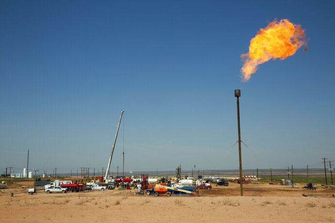 FILE- This May 24, 2018, file photo, shows a flare burning on the southwest corner of the Smith Ranch in Carlsbad, N.M. The oil boom in southeastern New Mexico may be attracting business to some communities but some chains say they are struggling to keep employees thanks to better-paying positions in the oilfield. (Robin Zielinski /The Las Cruces Sun News via AP, File)
