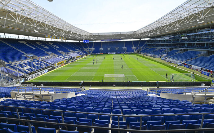 Players of Hoffenheim and Hertha warm-up in the empty stadium prior to the Bundesliga soccer match between TSG 1899 Hoffenheim and Hertha BSC Berlin in Sinsheim, Germany, Saturday, May 16, 2020. The German Bundesliga becomes the world's first major soccer league to resume after a two-month suspension because of the coronavirus pandemic. (Thomas Kienzle/AFP pool via AP)