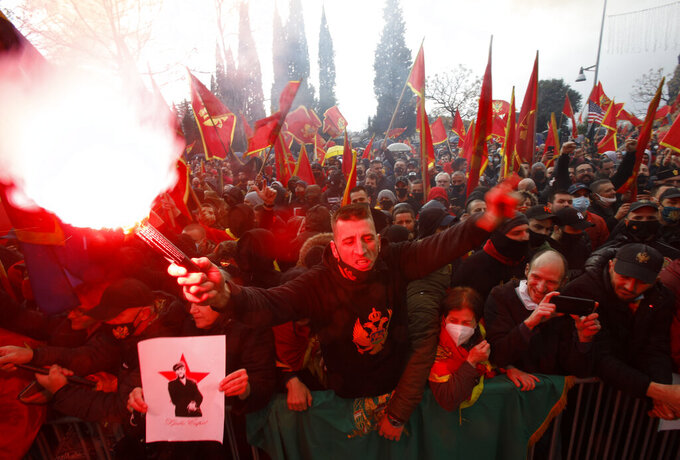 People shout slogans during a protest against the new government in Podgorica, Montenegro, Monday, Dec. 28, 2020. Several thousand people rallied Monday in Montenegro, accusing the new government of being pro-Serb because of its plans to amend a religious property law that is strongly opposed by the Serbian Orthodox Church. (AP Photo/Risto Bozovic)