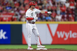 Cincinnati Reds' Kyle Farmer gestures to teammates after hitting a double during the fifth inning of the team's baseball game against the Los Angeles Dodgers in Cincinnati, Friday, Sept. 17, 2021. (AP Photo/Aaron Doster)