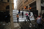 People climb a police barrier during anti-government protest following Tuesday's massive explosion which devastated Beirut, Lebanon, Sunday, Aug. 9. 2020. (AP Photo/Hassan Ammar)