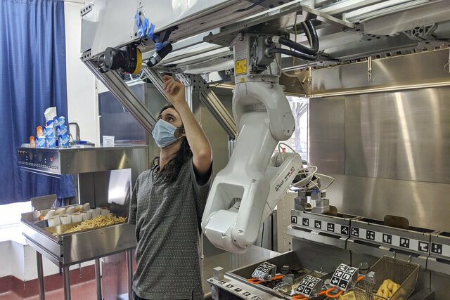 A technician makes an adjustment to a robot at Miso Robotics' White Castle test kitchen in Pasadena, Calif., Thursday, July 9, 2020. Robots that can flip burgers, make salads and even bake bread are in growing demand as virus-wary kitchens try to put some distance between workers and customers. Starting this fall, the White Castle burger chain will test the robot arm that can cook french fries and other foods.  The robot, dubbed Flippy, is made by Pasadena, California-based Miso Robotics.  (Miso Robotics via AP)