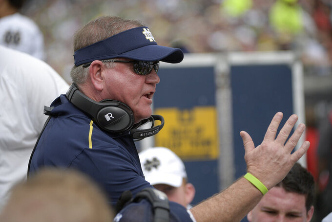 File-Notre Dame head coach Brian Kelly talks to players at the bench during the Camping World Bowl NCAA college football game against Iowa State Saturday, Dec. 28, 2019, in Orlando, Fla. The 58-year-old Kelly begins his 11th season at Notre Dame when the 10th-ranked Fighting Irish, taking a one-year sabbatical from football independence to join the Atlantic Coast Conference race, open against league rival Duke Sept. 12 at Notre Dame Stadium.  (AP Photo/Phelan M. Ebenhack, File)