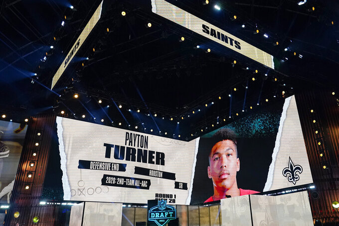 An image of Houston defensive end Payton Turner is displayed on stage after he was chosen by the New Orleans Saints with the 28th pick in the first round of the NFL football draft Thursday April 29, 2021, in Cleveland. (AP Photo/Tony Dejak)