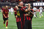 Atlanta United defender Julian Gressel (24) celebrates a goal by defender Franco Escobar, right, during the second half of round one of an MLS Cup playoff soccer game against the New England Revolution, Saturday, Oct. 19, 2019, in Atlanta. Atlanta United won 1-0. (AP Photo/John Amis)
