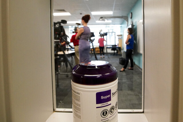 A container of sanitizing wipes sits at the entrance of a second grade classroom as media members attend a demonstration of a socially-distanced classroom at A.J. Whittenberg Elementary School of Engineering Monday, July 20, 2020, in Greenville, S.C. (AP Photo/Chris Carlson)