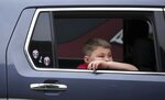 Fifth grader Karson Spencer waits in his car to enter Wayman Tisdale Fine Arts Academy on the first day of school Thursday, Aug. 19, 2021 in Tulsa, Okla. (Mike Simons/Tulsa World via AP)