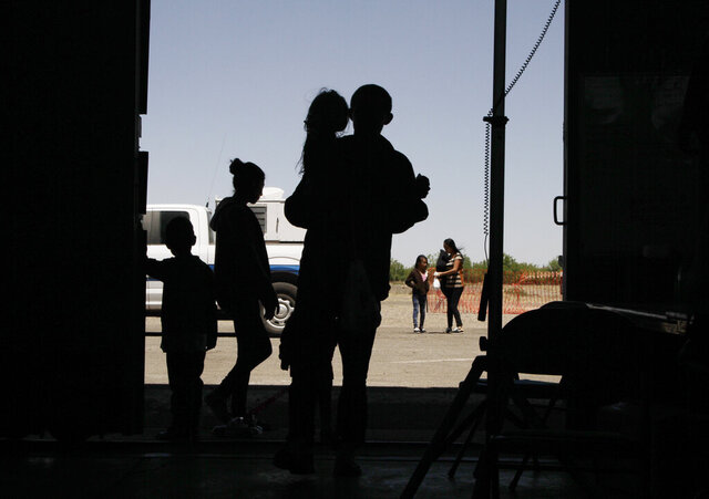 FILE - In this May 22, 2019 file photo migrants mainly from Central America guide their children through the entrance of a World War II-era bomber hanger in Deming, N.M. U.S. lawyers said Wednesday, Dec. 11, 2019, they want a judge to dismiss claims by New Mexico that immigration officials shirked their duties earlier this year by quickly releasing thousands of mostly Central American migrants into communities after they crossed into the United States. (AP Photo/Cedar Attanasio, File)
