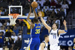 Golden State Warriors forward Kevin Durant (35) shoots as Dallas Mavericks forward Luka Doncic (77) defends in the first half of an NBA basketball game Saturday, March 23, 2019, in Oakland, Calif. (AP Photo/John Hefti)