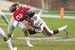 Auburn linebacker Colby Wooden (25) upends Mississippi quarterback Matt Corral (2) during the second half of an NCAA college football game in Oxford, Miss., Saturday, Oct. 24, 2020. (AP Photo/Rogelio V. Solis)