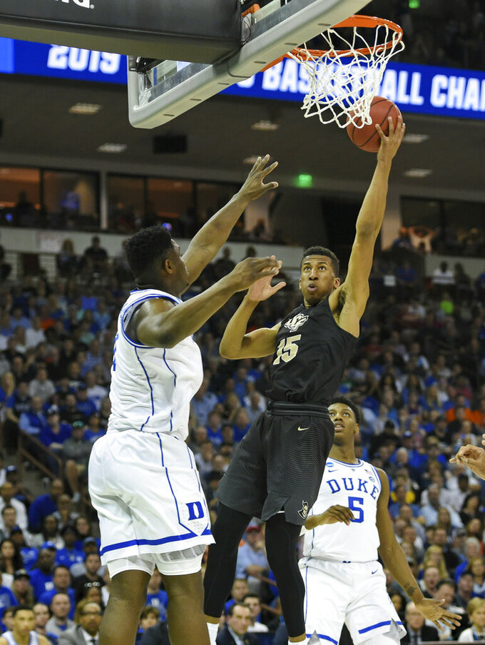 Central Florida's Aubrey Dawkins (15) shoots while defended by Duke's Zion Williamson, left, and RJ Barrett during the first half of a first round men's college basketball game in the NCAA Tournament in Columbia, S.C. Sunday, March 24, 2019. (AP Photo/Richard Shiro)