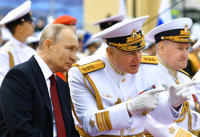 Russian President Vladimir Putin, left, listens to Admiral Nikolai Yevmenov, Commander-in-Chief of the Russian Navy, second right, while watching the Navy Day parade in St.Petersburg, Russia, Sunday, July 25, 2021. (Alexei Nikolsky, Sputnik, Kremlin Pool Photo via AP)