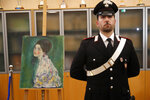 An Italian Carabiniere, paramilitary police officer, stands near a painting which was found last December near an art gallery and believed to be the missing Gustav Klimt's painting 'Portrait of a Lady' during a press conference in Piacenza, Italy, Friday, Jan. 17, 2020. Art experts have confirmed that a stolen painting discovered hidden inside an Italian art gallery's walls is Gustav Klimt's