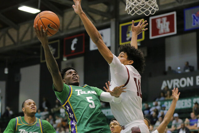 FILE - In this Feb. 12, 2020, file photo, Tulane guard Teshaun Hightower (5) is guarded by Temple forward Jake Forrester (10) during the first half of an NCAA college basketball game in New Orleans. Henry County Jail records show 22-year-old Teshaun Hightower was booked into jail Saturday, April 25, 2020, on multiple charges, including murder and aggravated assault. Hightower is a junior guard who led the Green Wave in scoring last season. (David Grunfeld/The Advocate via AP, File)/The Advocate via AP)