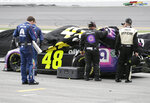 Jimmie Johnson's crew covers up his car as inclement weather moves in to delay the finish of the NASCAR Cup Series auto race at Daytona International Speedway, Sunday, July 7, 2019, in Daytona Beach, Fla. (AP Photo/Terry Renna)