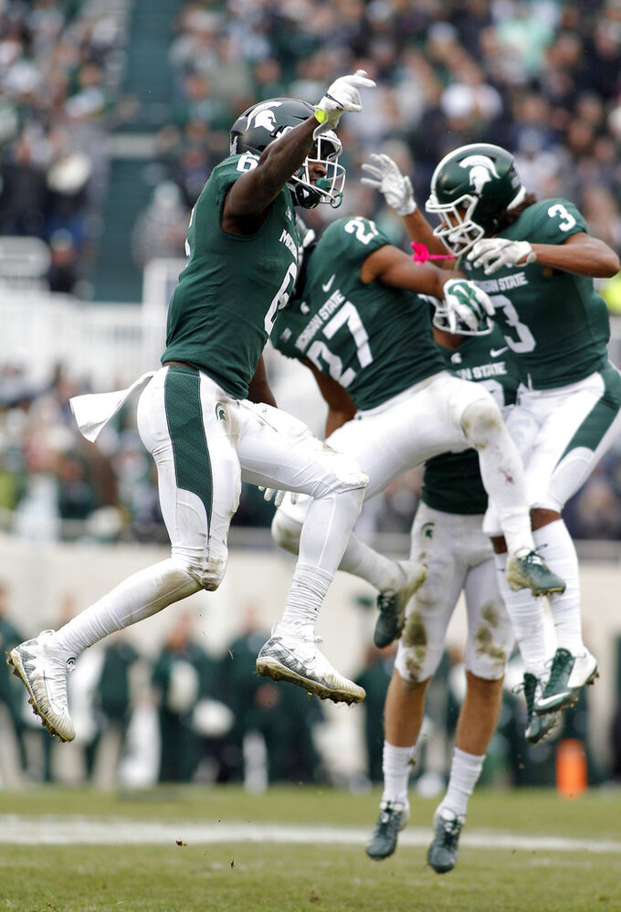 Michigan State's David Dowell, left, Khari Willis (27) and Xavier Henderson (3) celebrate a stop and a turnover on downs against Purdue during the fourth quarter of an NCAA college football game, Saturday, Oct. 27, 2018, in East Lansing, Mich. Michigan State won 23-13. (AP Photo/Al Goldis)
