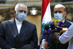 Lebanese Foreign Minister Charbel Wehbe, left, speaks during a joint press conference with his Iranian counterpart Mohammad Javad Zarif, outside the Lebanese foreign ministry damaged by last week's explosion that his the seaport of Beirut, Lebanon, Friday, Aug. 14, 2020. (AP Photo/Hussein Malla)