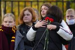 Students comfort each other as they gather outside the Perm State University following a campus shooting in Perm, about 1,100 kilometers (700 miles) east of Moscow, Russia, Tuesday, Sept. 21, 2021. A student opened fire at the university, leaving a number of people dead and injured, before being shot in a crossfire with police and detained. Beyond saying that he was a student, authorities offered no further information on his identity or a possible motive. (AP Photo/Dmitri Lovetsky)