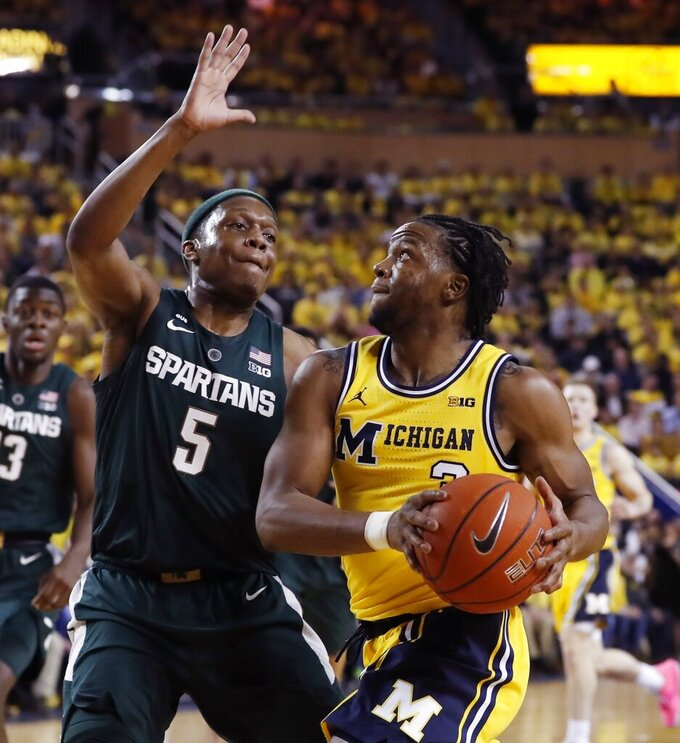 FILE - In this Feb. 24, 2019, file photo, Michigan guard Zavier Simpson (3) is defended by Michigan State guard Cassius Winston (5) during the first half of an NCAA college basketball game, in Ann Arbor, Mich. No. 9 Michigan State hosts No. 7 Michigan in their Big Ten regular season finale with at least a share of the conference title at stake. (AP Photo/Carlos Osorio, File)