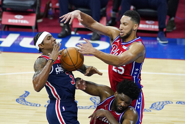 Washington Wizards' Bradley Beal, left, cannot get a shot past Philadelphia 76ers' Ben Simmons, top right, and Joel Embiid during the first half of an NBA basketball game, Wednesday, Dec. 23, 2020, in Philadelphia. (AP Photo/Matt Slocum)