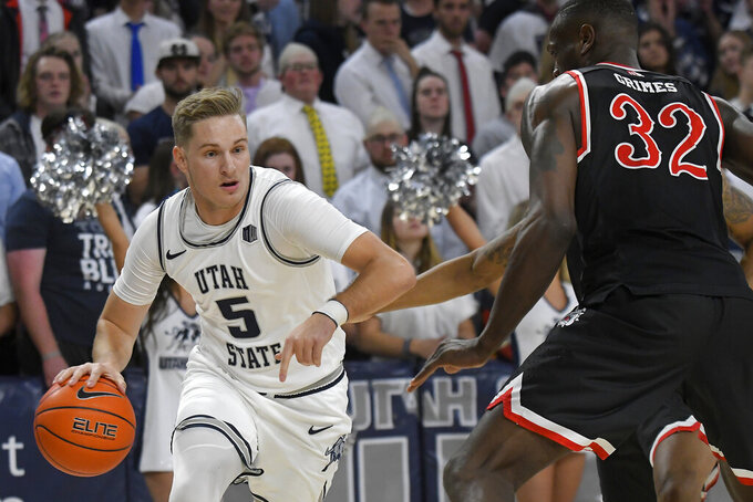 Utah State guard Sam Merrill (5) dribbles the ball as Fresno State forward Nate Grimes (32) defends during the first half of an NCAA college basketball game Saturday, Dec. 7, 2019, in Logan, Utah. (AP Photo/Eli Lucero)