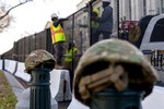 National Guard helmets are placed on top of barricades as workers install razor wire to the top of fencing on Capitol Hill in Washington, Thursday, Jan. 14, 2021. (AP Photo/Andrew Harnik)