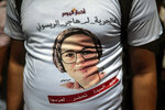 A journalist attends a demonstration outside a court in solidarity with detained journalist Hajar Raissouni, in Rabat, Morocco, Monday, Sept. 9, 2019. Words in Arabic read