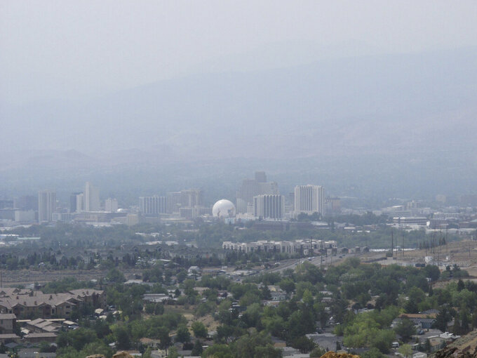 Smoke from wildfires in California blankets downtown Reno, Nev., Wednesday, Aug. 18, 2021, obscuring the Sierra range typically visible to the west. The 10 worst days recorded for small particulate air pollution over the past 22 years in the Reno-Sparks area all have occurred over the past 11 months, Washoe County Health District officials said during a wildfire roundtable that Sen. Catherine Cortez Masto, D-Nev., hosted in Reno. (AP Photo/Scott Sonner)