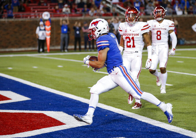 SMU wide receiver Tyler Page (4) scores a touchdown as Houston defensive back Gleson Sprewell (21) and linebacker Emeke Egbule (8) defend during the first half of an NCAA college football game Saturday, Nov. 3, 2018, in Dallas. (AP Photo/Brandon Wade)