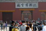 Visitors wearing face masks to help curb the spread of the coronavirus exit the Forbidden City during a weeklong holiday for the Oct. 1 National Day, in Beijing, Wednesday, Oct. 7, 2020. Chinese tourists took 425 million domestic trips in the first half of the eight-day National Day holiday, generating $45.9 billion in tourism revenue, according to China's ministry of culture and tourism. The holiday this year, which coincides with the Mid-Autumn Festival, will be a litmus test of whether China's tourism industry can bounce back after being battered by COVID-19. (AP Photo/Andy Wong)