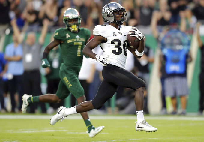 Central Florida's Greg McCrae runs past South Florida's Mike Hampton to score a touchdown during the first half of an NCAA college football game Friday, Nov. 23, 2018, in Tampa, Fla. (AP Photo/Mike Carlson)