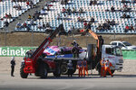 Track marshals remove the car of the Racing Point driver Lance Stroll of Canada during the second practice session prior to the Formula One Portuguese Grand Prix at the Algarve International Circuit in Portimao, Portugal, Friday, Oct. 23, 2020. The Formula One Portuguese Grand Prix will take place on Sunday. (Jose Sena Goulao, Pool via AP)