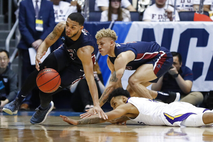 Fairleigh Dickinson's Darnell Edge, left, scrambles after a loose ball against Prairie View A&M's Dennis Jones, bottom right, during the first half of a First Four game of the NCAA college basketball tournament, Tuesday, March 19, 2019, in Dayton, Ohio. (AP Photo/John Minchillo)