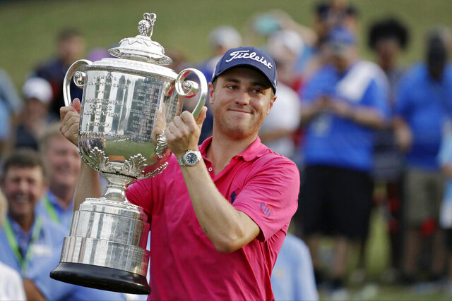 FILE - In this Aug. 13, 2017, file photo, Justin Thomas poses with the Wanamaker Trophy after winning the PGA Championship golf tournament at the Quail Hollow Club in Charlotte, N.C. Justin Thomas can put down the driver and grab a controller: The former PGA Championship winner made the cover of the
