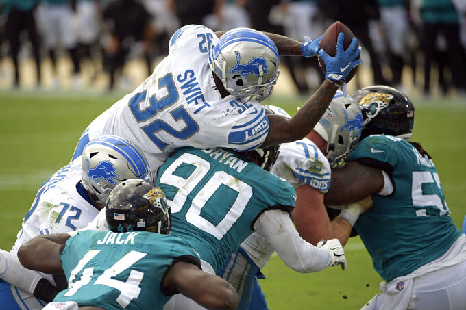 Detroit Lions running back D'Andre Swift (32) leaps over Jacksonville Jaguars linebacker Myles Jack (44) and defensive tackle Taven Bryan (90) for a touchdown during the first half of an NFL football game, Sunday, Oct. 18, 2020, in Jacksonville, Fla. (AP Photo/Phelan M. Ebenhack)