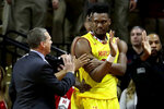 Maryland head coach Mark Turgeon, left, talks to forward Bruno Fernando, right, who is restrained by teammate Jalen Smith, back, during a play against Rutgers in the first half of an NCAA college basketball game, Saturday, Jan. 5, 2019, in Piscataway, N.J. Rutgers' Montez Mathis was called for a technical foul on Fernando during the play. (AP Photo/Julio Cortez)