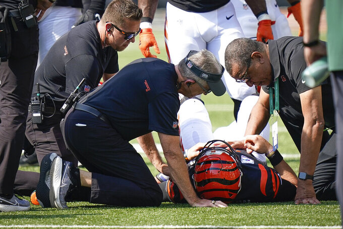 Cincinnati Bengals quarterback Joe Burrow is tended to by the medical staff after being injured on a play in the first half of an NFL football game against the Green in Cincinnati, Sunday, Oct. 10, 2021. (AP Photo/Bryan Woolston)